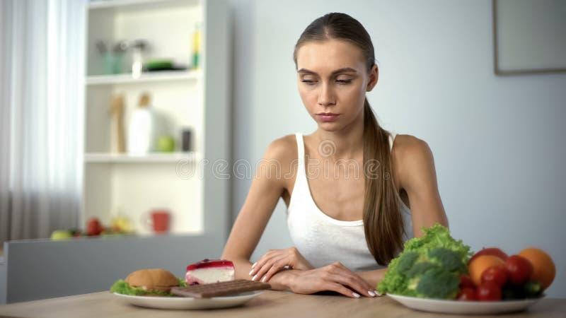 Dunne vrouw die tussen ongezonde kost en gezonde groenten, aarzeling, dieet kiezen royalty-vrije stock foto