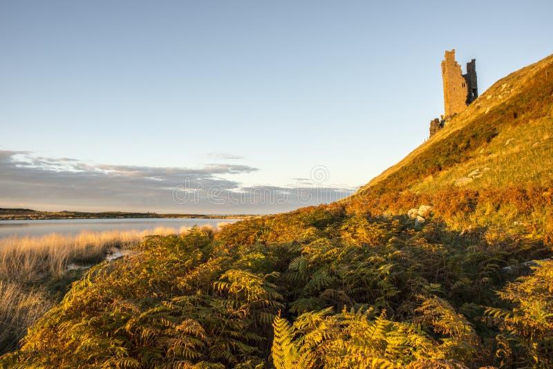 Dunstanburgh废墟在日落的秋天 免版税库存图片