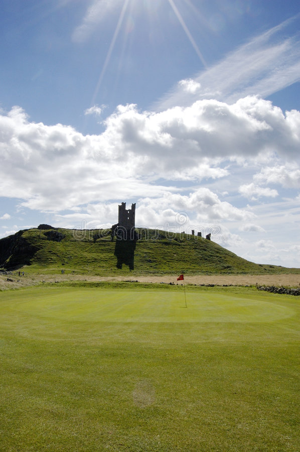 Dunstanburgh Castle and Golf green vertical. One of the greens of Embleton Golf course and Dunstanburgh Castle royalty free stock photo