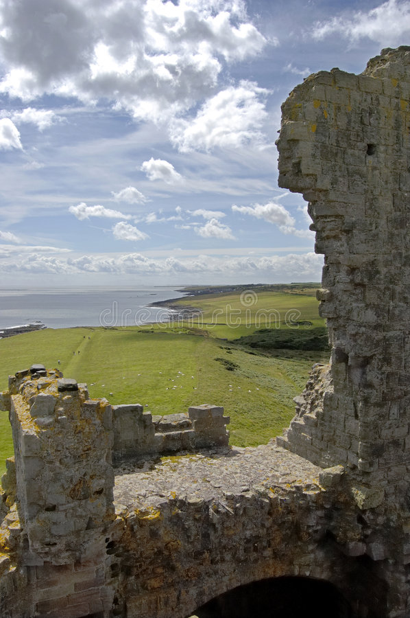 Dunstanburgh Castle wall and coastline. The crumbling walls of Dunstanburgh Castle with the northumberland coast beyond royalty free stock photography
