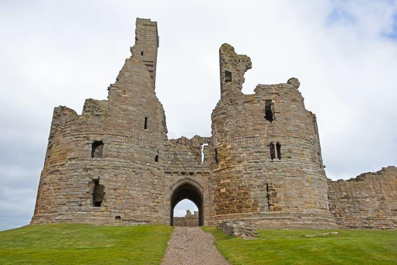 Dunstanburgh slott - fördärvar arkivfoto