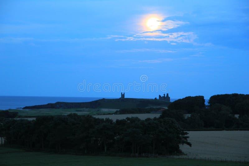 Dunstanburgh slott på natten arkivbild