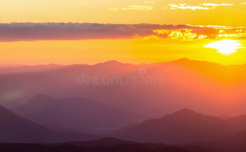 Dunstiger Gebirgszug mit drastischem Sonnenunterganghimmel stockfoto