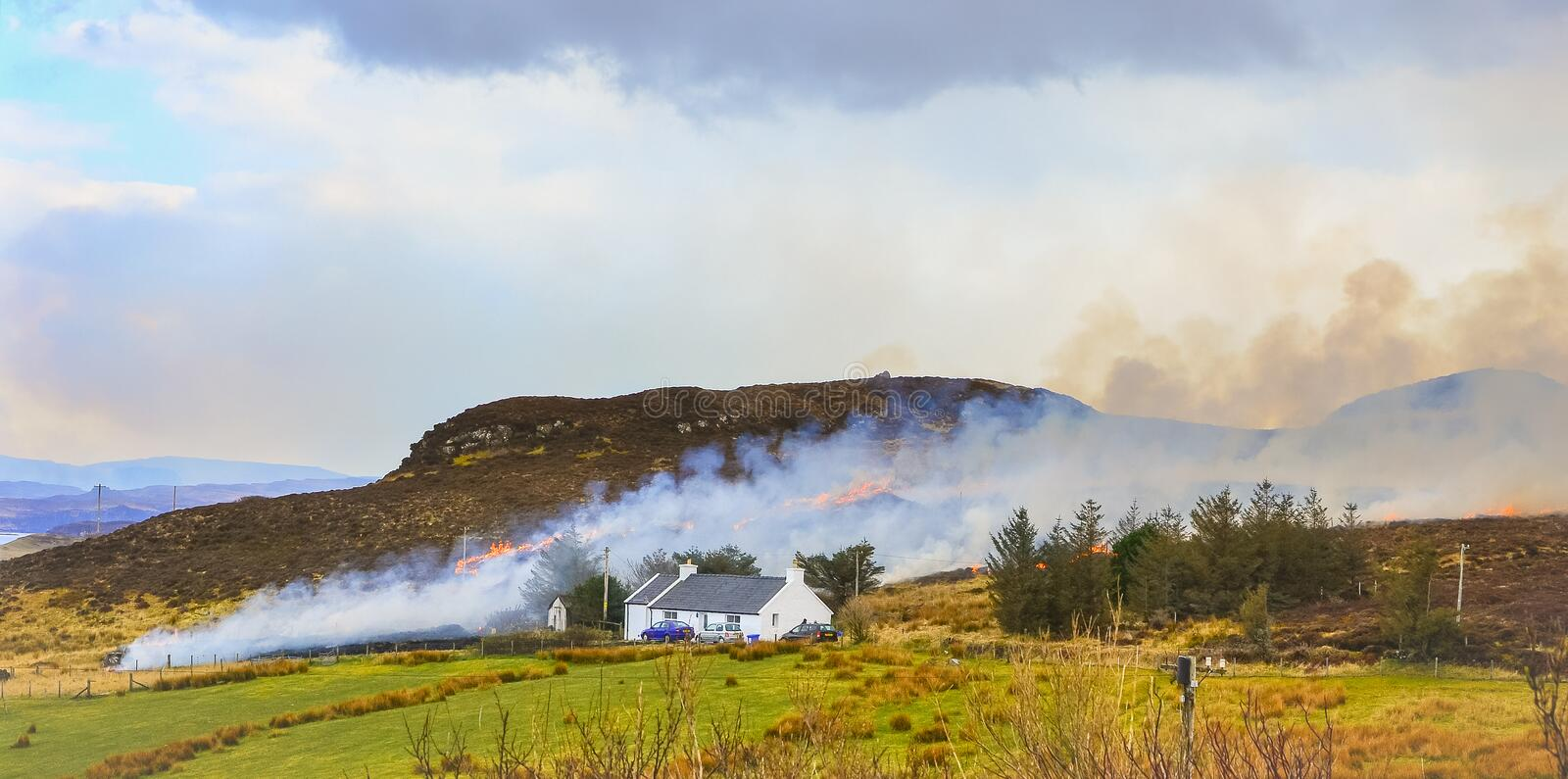 Dunvegan/Scotland, March 2014: Fire brigade trying to control a dry grass and reeds fire near residential buildings stock photography