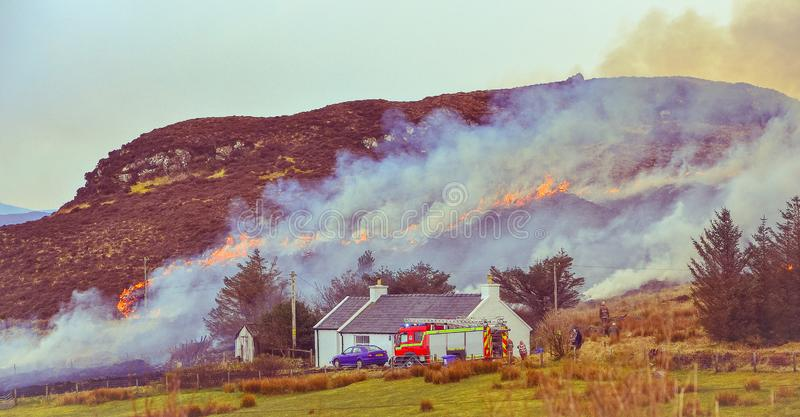 Dunvegan/Scotland, March 2014: Fire brigade trying to control a dry grass and reeds fire near residential buildings royalty free stock photos