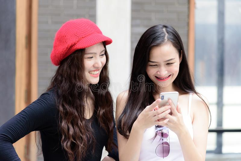 Duo asian portrait girl have playing a mobile phone and talking stock photos