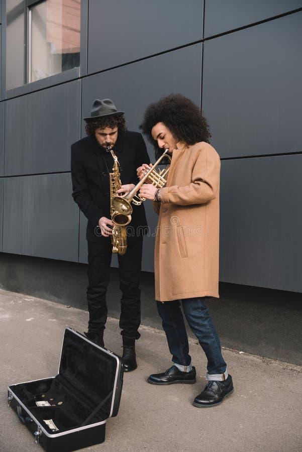 Duo von den stilvollen Straßenmusikern, die Trompete spielen lizenzfreies stockbild