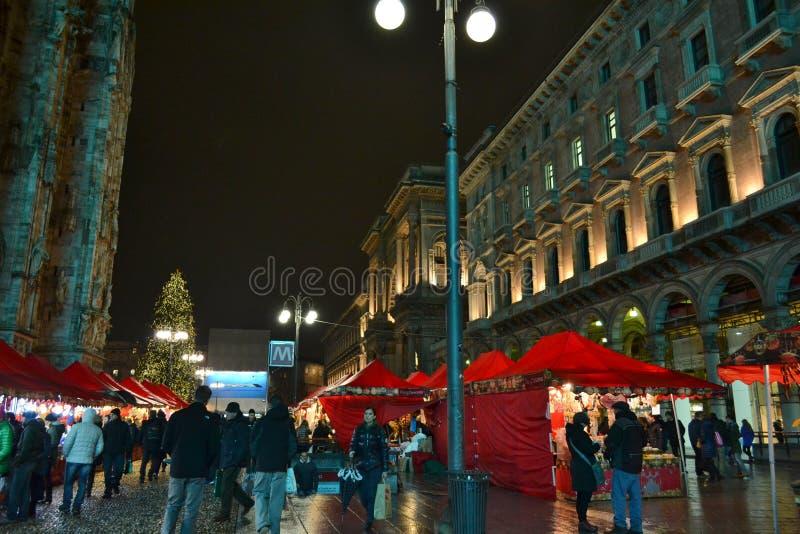 Duomo της αγοράς Χριστουγέννων του Μιλάνου με τα κόκκινα gazebos, το κατάστημα Rinascente και το περπάτημα ανθρώπων στοκ φωτογραφία