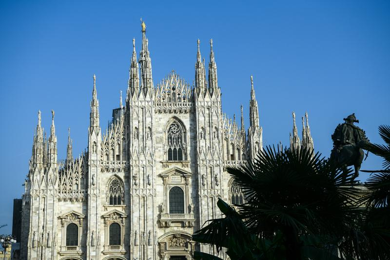 The Duomo Cathedral in Milan, Italy with the newly planted palm trees and the equestrian statue of Vittorio Emanuele II. Clear blue sky. Madonnina statue on stock photo