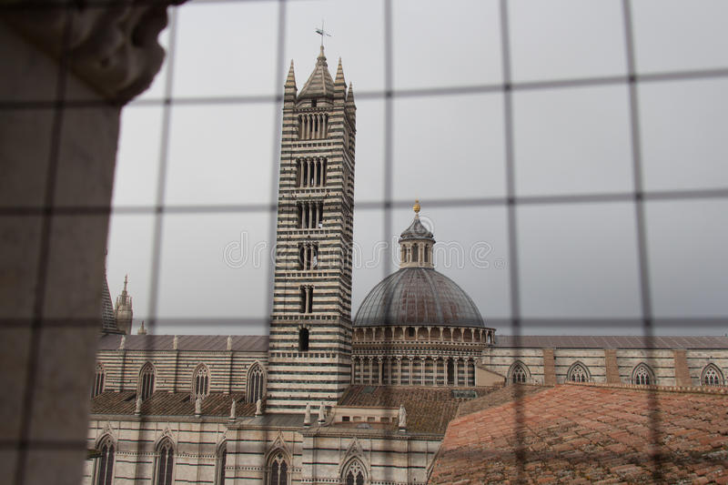 Duomo di Siena and bell tower. View from iron grid window. Tuscany, Italy. royalty free stock images