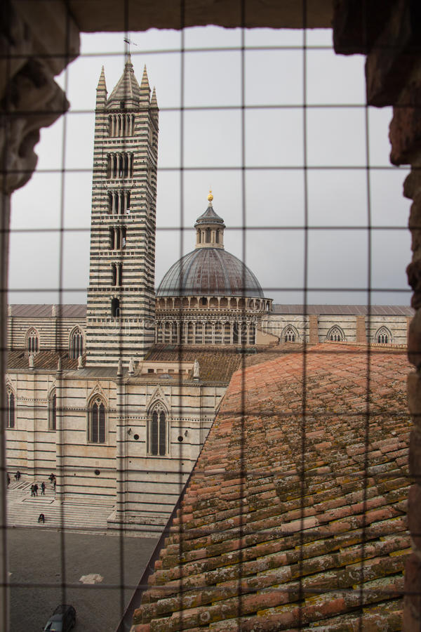 Duomo di Siena and bell tower. View from iron grid window. Tuscany, Italy. royalty free stock photo