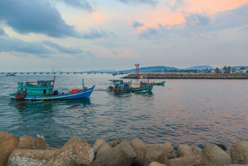 Duong Dong stad, Phu Quoc, Vietnam - December 2018: skepp i havet nära hamn med vågbrytaren, härliga moln och solnedgång royaltyfri fotografi