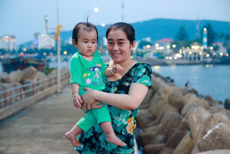 Duong Dong stad, Phu Quoc, Vietnam - December 2018: vietnamesisk kvinna med småbarnet nära på vågbrytaren royaltyfri fotografi