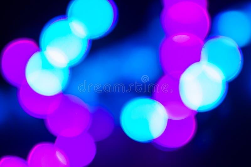 Duotone blå och purpurfärgad abstraktion av oskarpa neonljus på svart royaltyfri bild