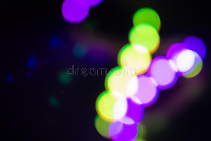 Duotone green and purple blurry neon lights on black. Night party concept stock image