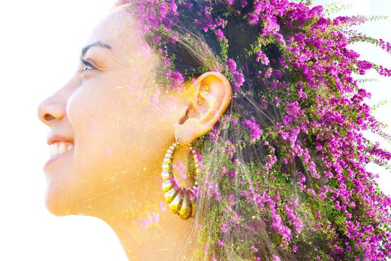 A dupla exposição fecha o retrato de uma jovem bonita entretecida com flores roxas brilhantes Bougainvillea, aparentemente imagem de stock