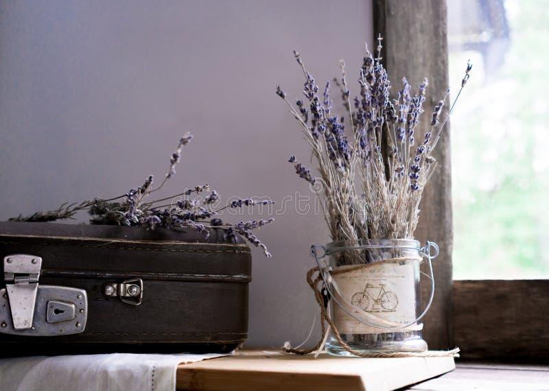 Durée toujours 1 cru vieux valise et brins de lavande sur le fond de vieilles fenêtres au jardin nuances lilas images stock