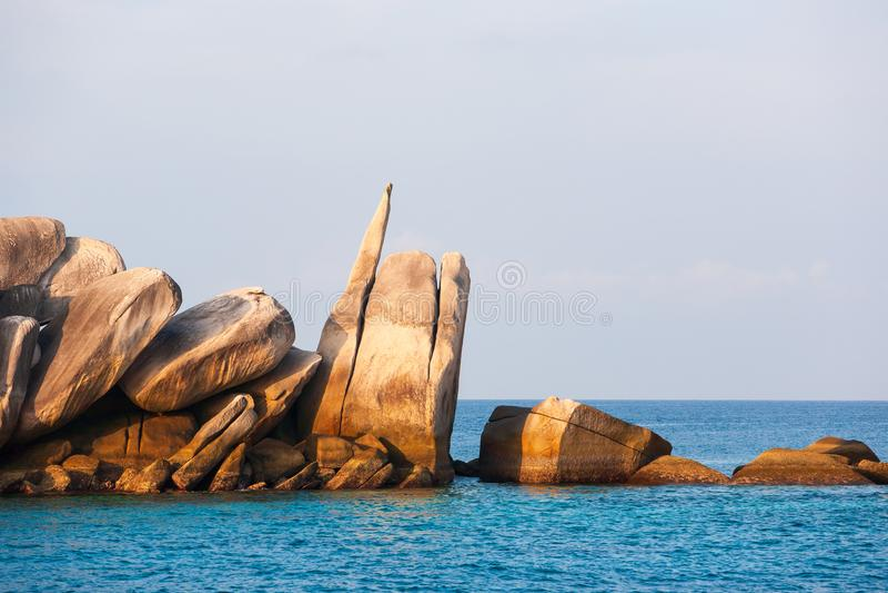 Dur et offre, belles roches dans l'océan bleu Lumière de coucher du soleil Le Su photographie stock libre de droits