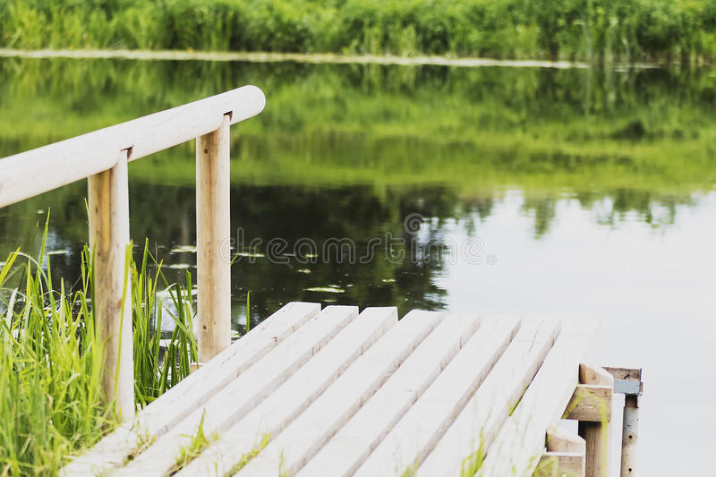 , durable wooden dock on the river for fishing. Beautiful, durable wooden dock on the river for fishing royalty free stock image