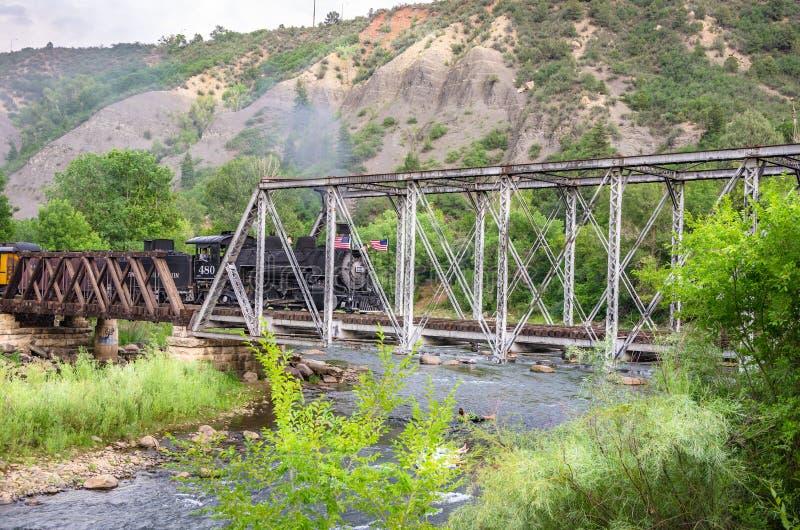 Durangoen & drevet för järnväg Silverton för smalt mått som korsar en metallbro royaltyfri fotografi