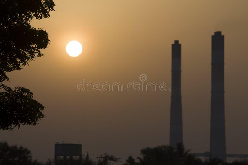 Durante horas de oro de la puesta del sol con el fondo colorido de la silueta del cielo y de la chimenea de la central térmico  imagen de archivo