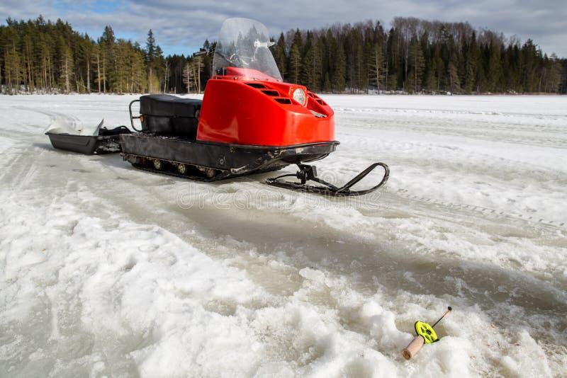 Durante l'inverno la canna da pesca si trova sul ghiaccio vicino al gatto delle nevi fotografia stock libera da diritti