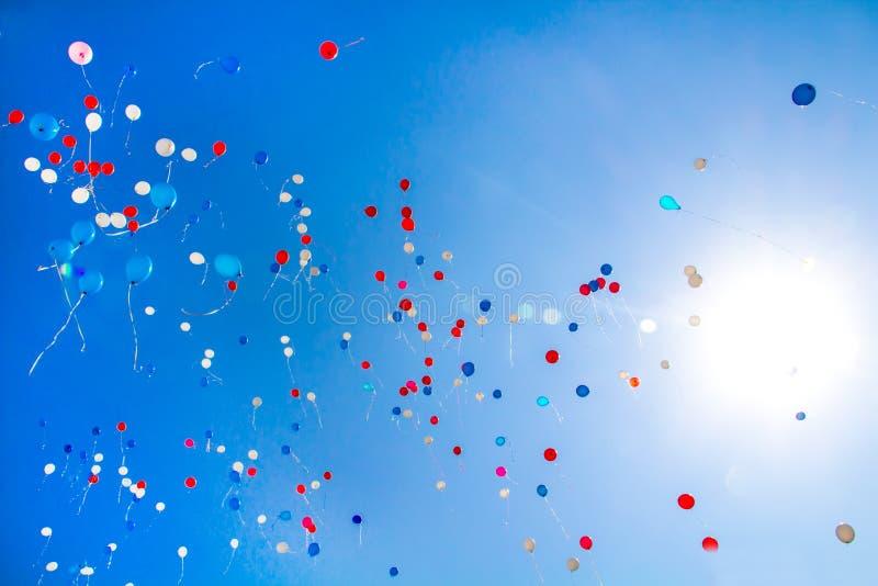 Durante la celebración del día de fiesta los globos coloridos vuelan en el cielo foto de archivo libre de regalías