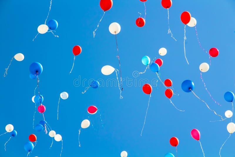 Durante la celebración del día de fiesta los globos coloridos vuelan en el cielo fotos de archivo