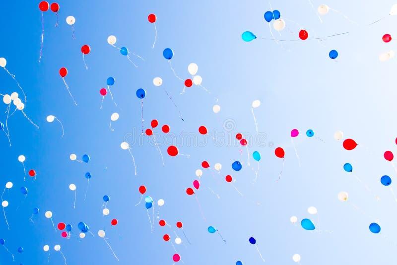 Durante la celebración del día de fiesta los globos coloridos vuelan en el cielo imagenes de archivo
