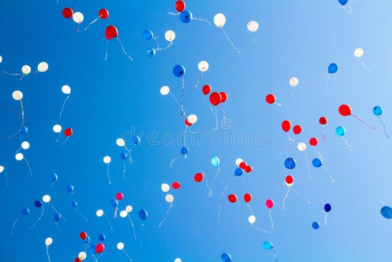 Durante la celebración del día de fiesta los globos coloridos vuelan en el cielo foto de archivo