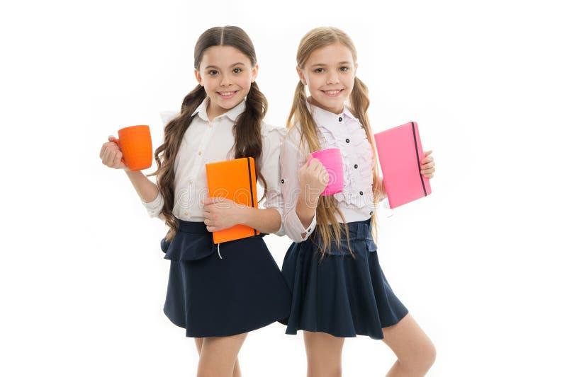 Durante la loro ora del pranzo Scolare sveglie che tengono le tazze ed i libri Piccole ragazze che godono della loro refezione In immagine stock libera da diritti