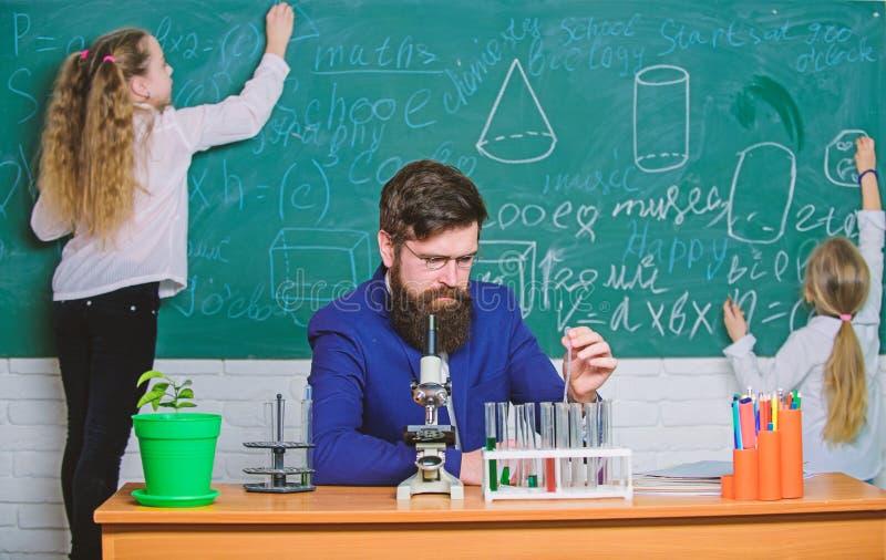 Durante tiempo de la clase Profesor y peque?os alumnos en clase del laboratorio Clase de qu?mica barbuda de la ense?anza del homb foto de archivo
