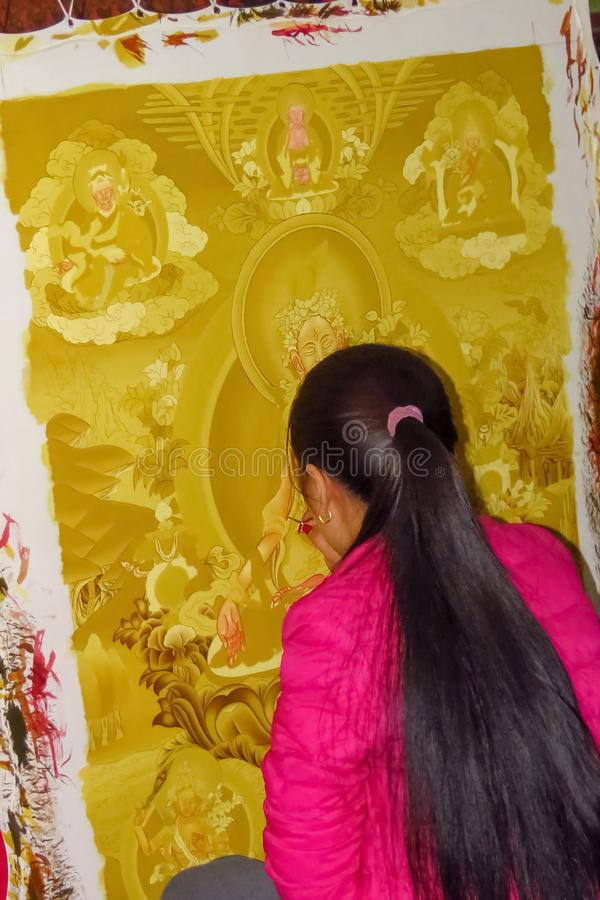 Young woman painting a thanka, a Tibetan Buddhist religious painting, Durbar Square, Bhaktapur, Nepal. Durbar Square, Bhaktapur, Nepal - 11/21/2017: traditional royalty free stock photos
