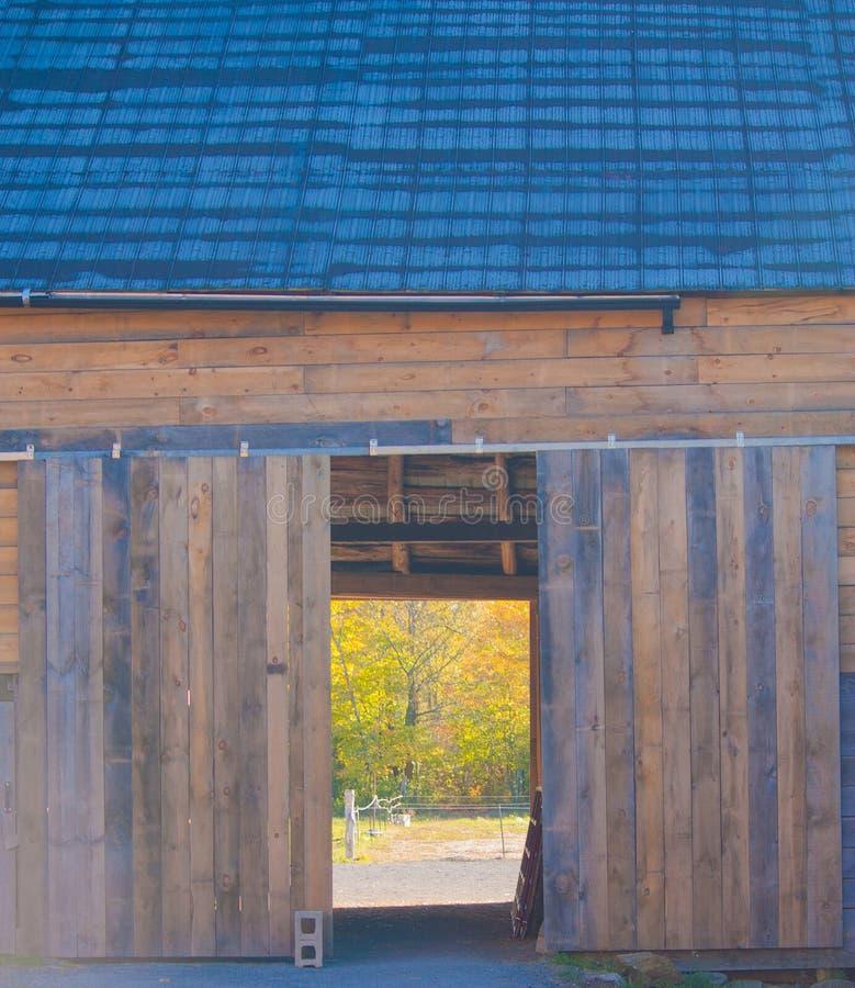 Durch eine offene Scheunentür zur Weide jenseits schauen stockfoto