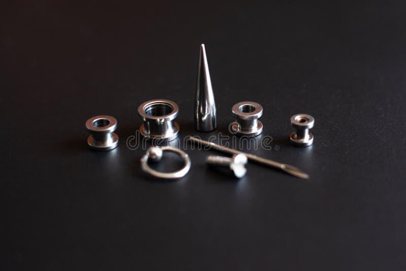 Durchbohrende Zusätze auf einem rostfreien Schmuck des schwarzen Hintergrundes Metallfür Durchbohrenliebhaber lizenzfreie stockfotografie