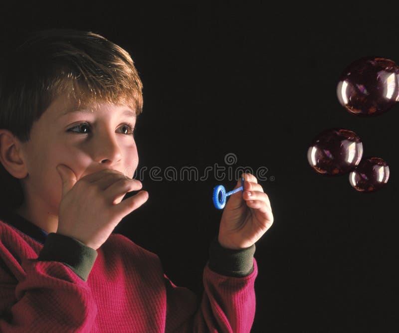 Durchbrennenluftblasen des jungen Jungen stockfoto