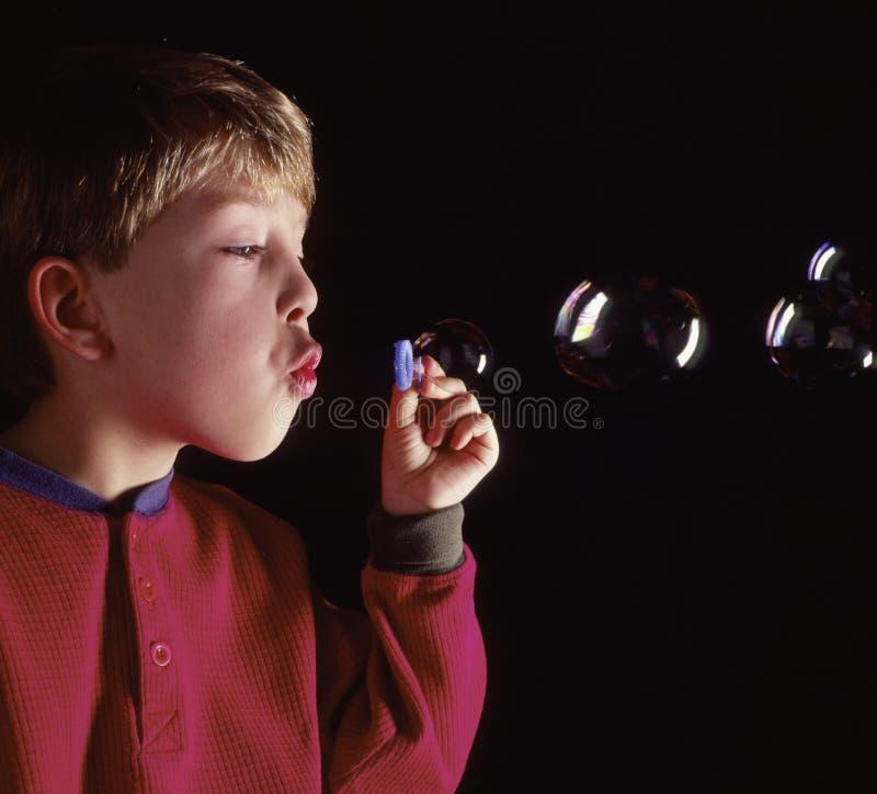 Durchbrennenluftblasen des jungen kaukasischen Jungen lizenzfreies stockfoto