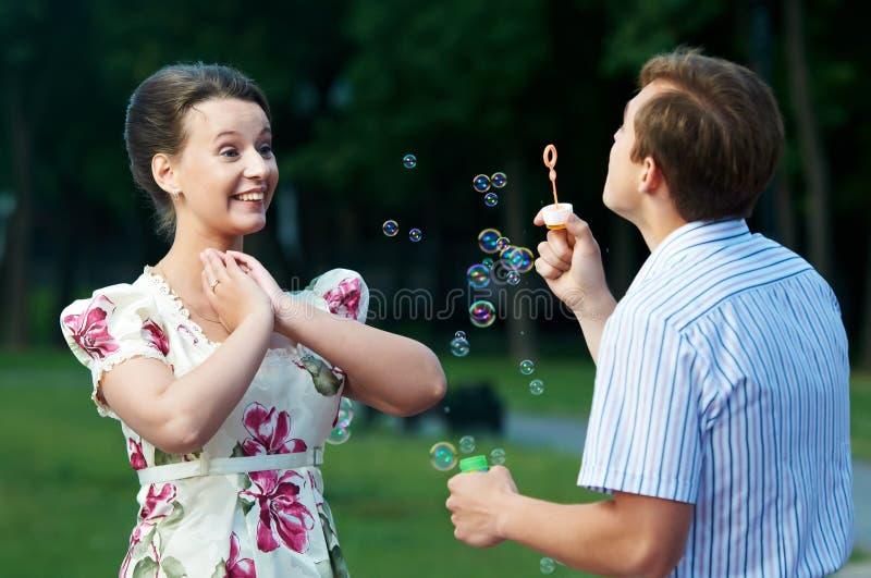 Durchbrennenseifenluftblasen der glücklichen Paare lizenzfreies stockfoto