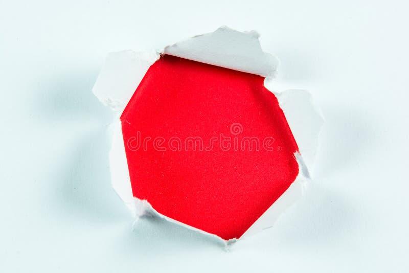 Durchbruch heftiges großes schwarzes Loch im roten Papier lizenzfreie stockfotografie