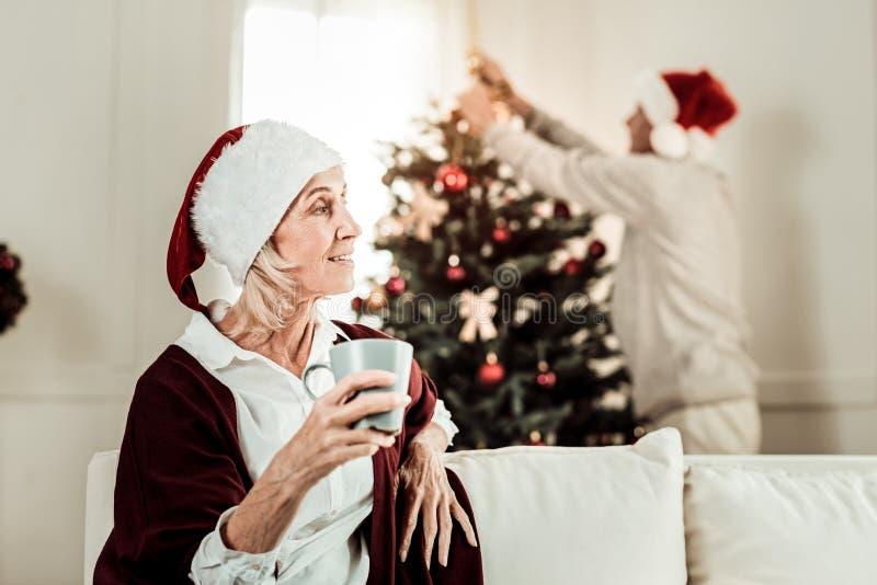 Durchdachte ältere Frau, die eine Schale sitzt und hält lizenzfreies stockbild
