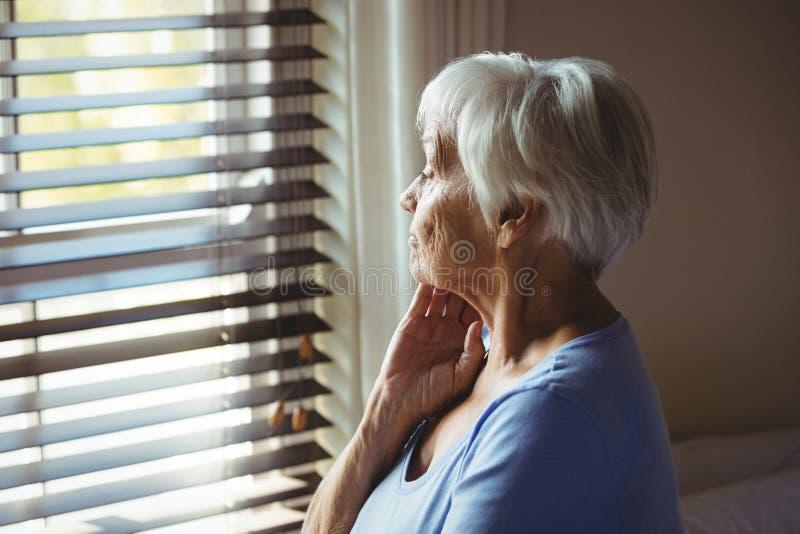 Durchdachte ältere Frau, die heraus vom Fenster schaut lizenzfreie stockbilder