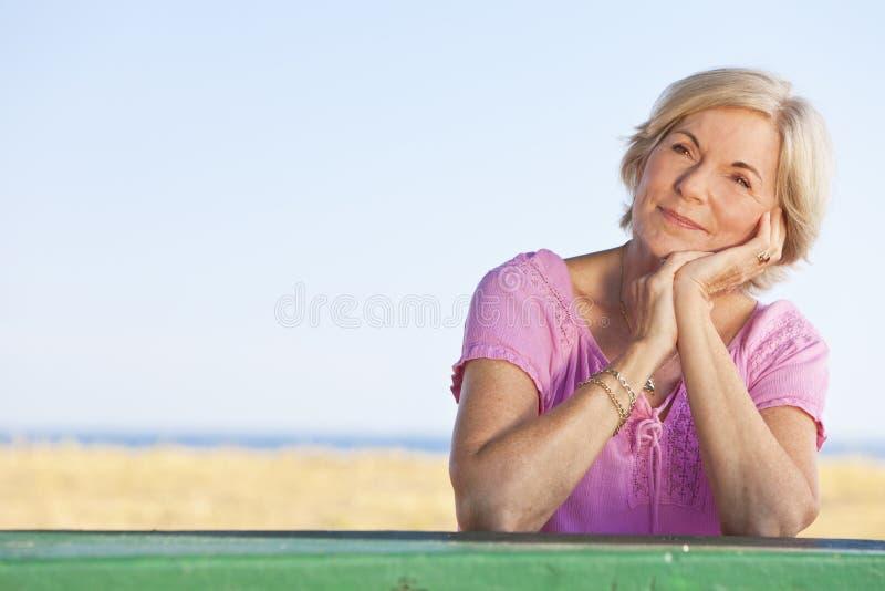 Durchdachte ältere Frau draußen am Tisch lizenzfreie stockfotografie