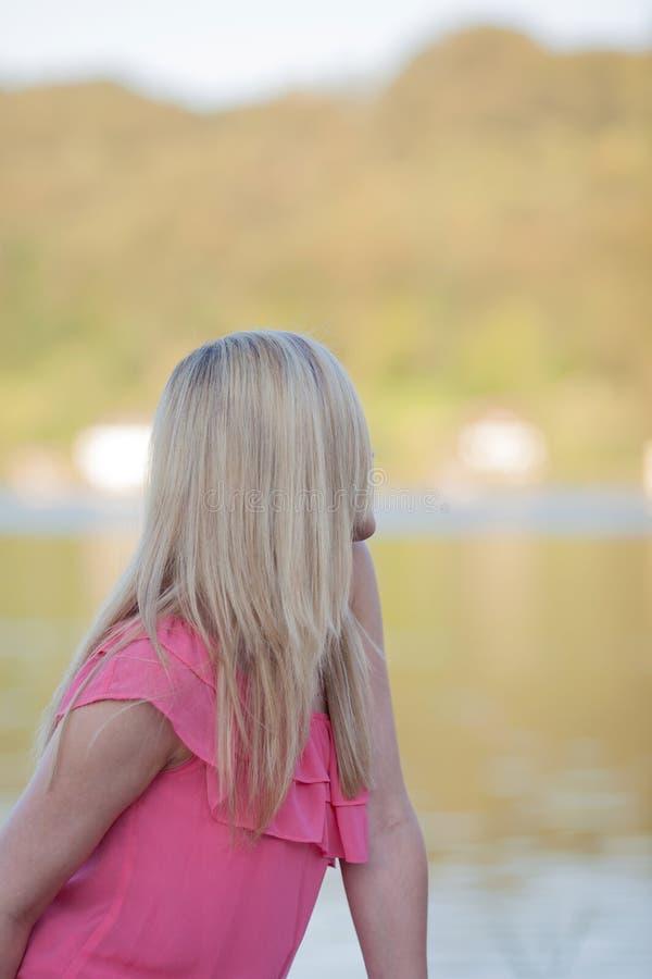 Durchdachte blonde Frau, die am Seeufer sich entspannt stockfotos