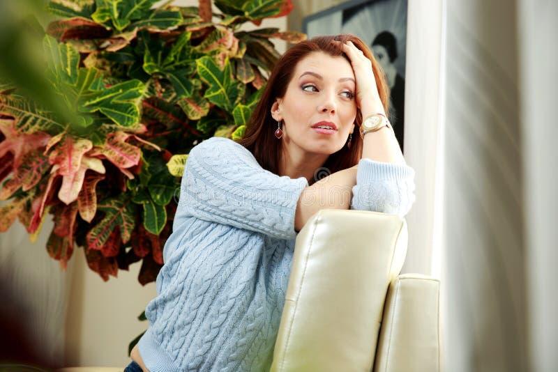 Durchdachte Frau, die auf dem Sofa sitzt stockbilder