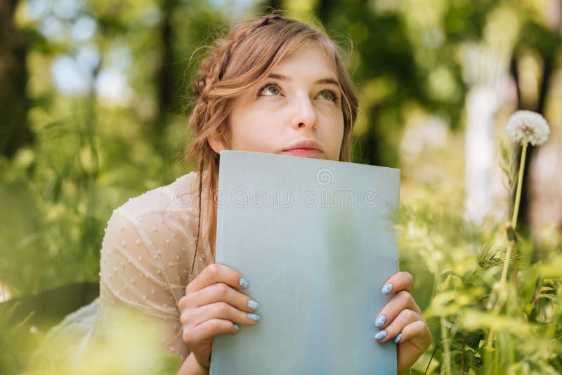 Durchdachte Frau, die auf Gras liegt und leere Zeitschrift hält stockfoto