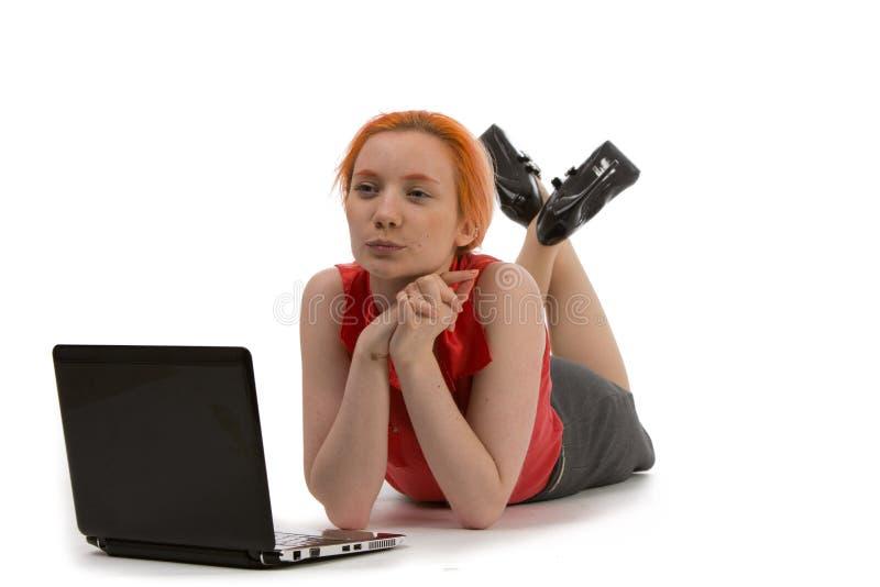 Durchdachte Frau, die an einem Laptop arbeitet lizenzfreie stockbilder