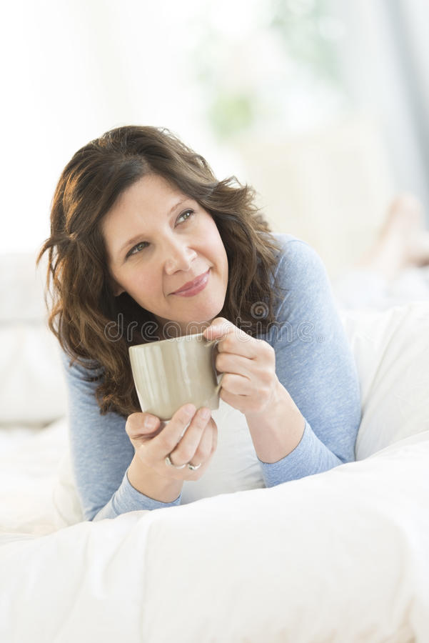 Durchdachte Frau, die Kaffeetasse im Bett hält stockbilder
