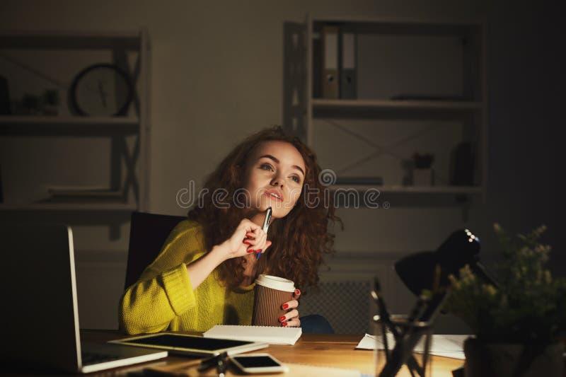 Durchdachte Frau, die zu Hause bis späten Abend arbeitet stockfoto