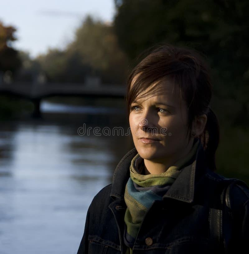 Durchdachte Frau durch Fluss lizenzfreies stockfoto