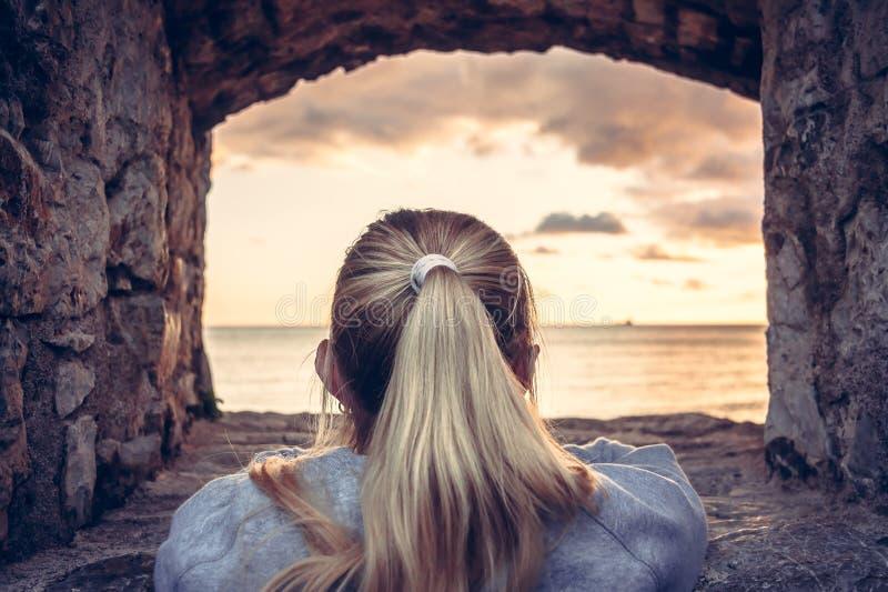 Durchdachte Frau gewidmet in Betrachtung des schönen Sonnenuntergangs über Meer durch Fenster des alten Schlosses mit drastischem lizenzfreies stockbild